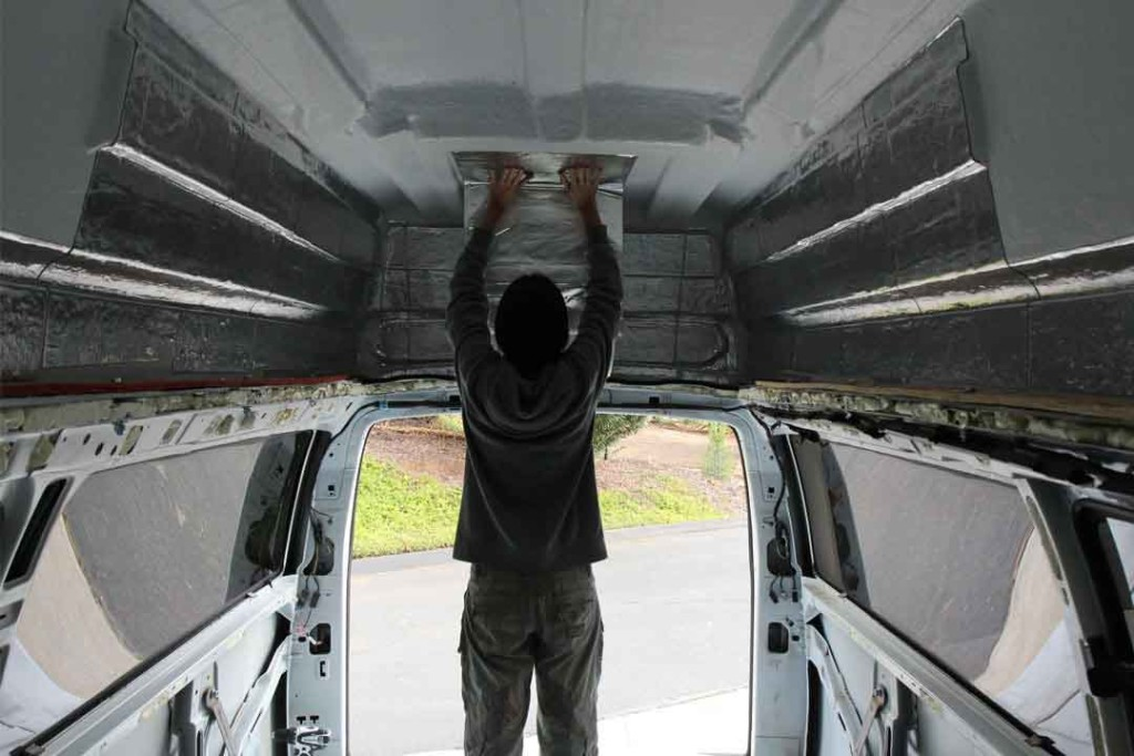 me applying sound deadening to the ceiling