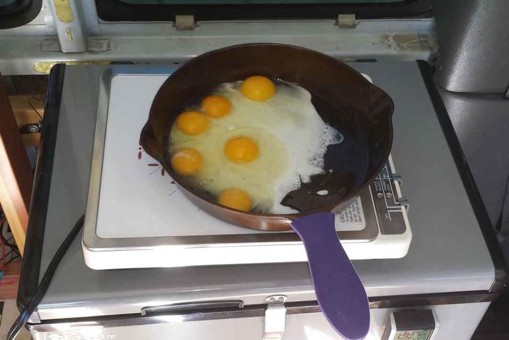 Frying eggs on induction cooktop inside van