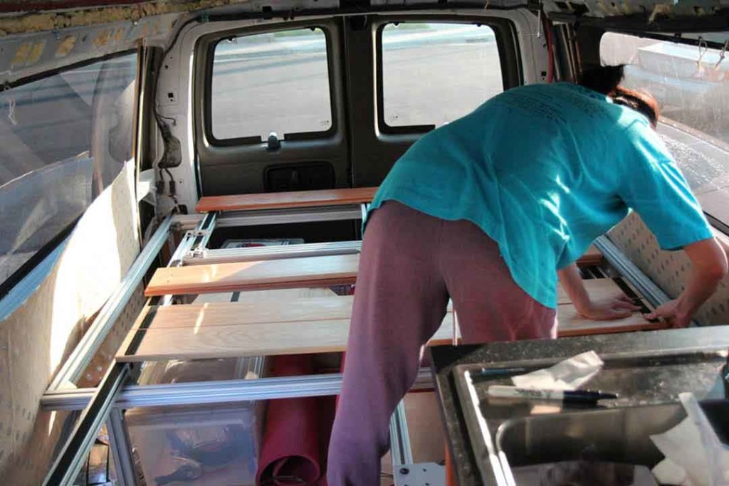 Attaching slats to the bed frame in the van